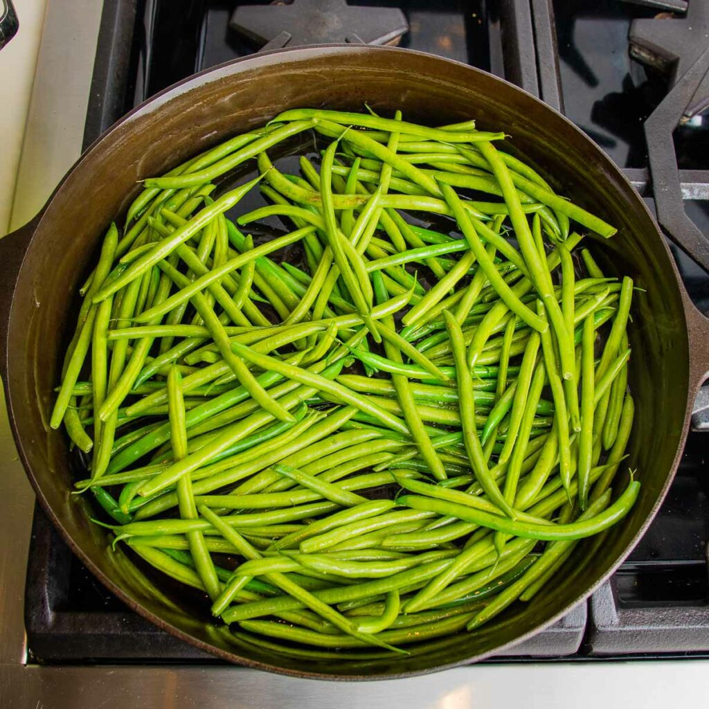 Cast iron pan filled with green beans.
