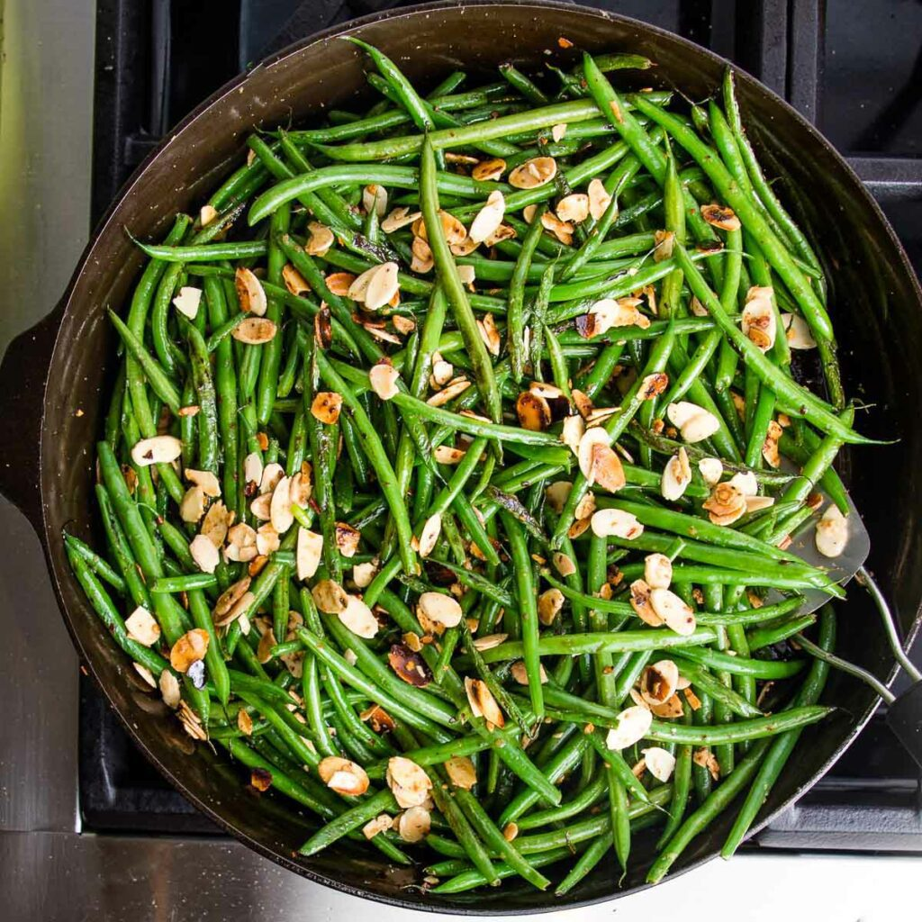 Cast iron skillet with green beans, almonds, garlic and crushed red pepper.