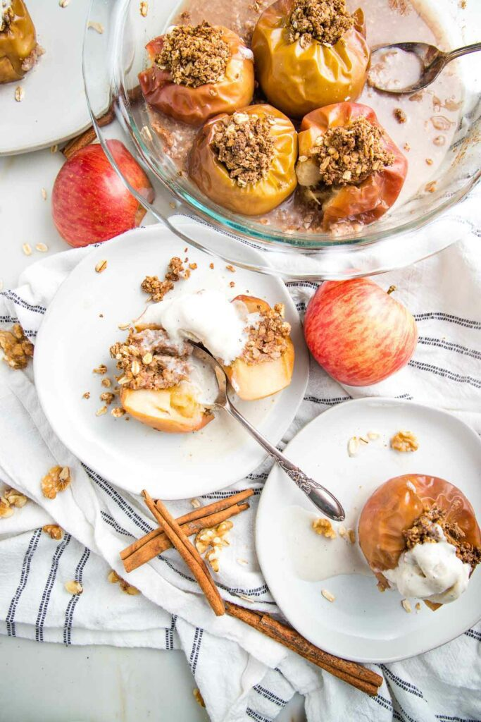 White plate with a baked apple, stuffed with oatmeal mixture cut in half and topped with vanilla ice cream.  There is another plate on the bottom right with a whole baked apple, a glass pie plate iwth additional baked apples and the background is scattered with cinnamon sticks, red uncooked apples and crumbs.