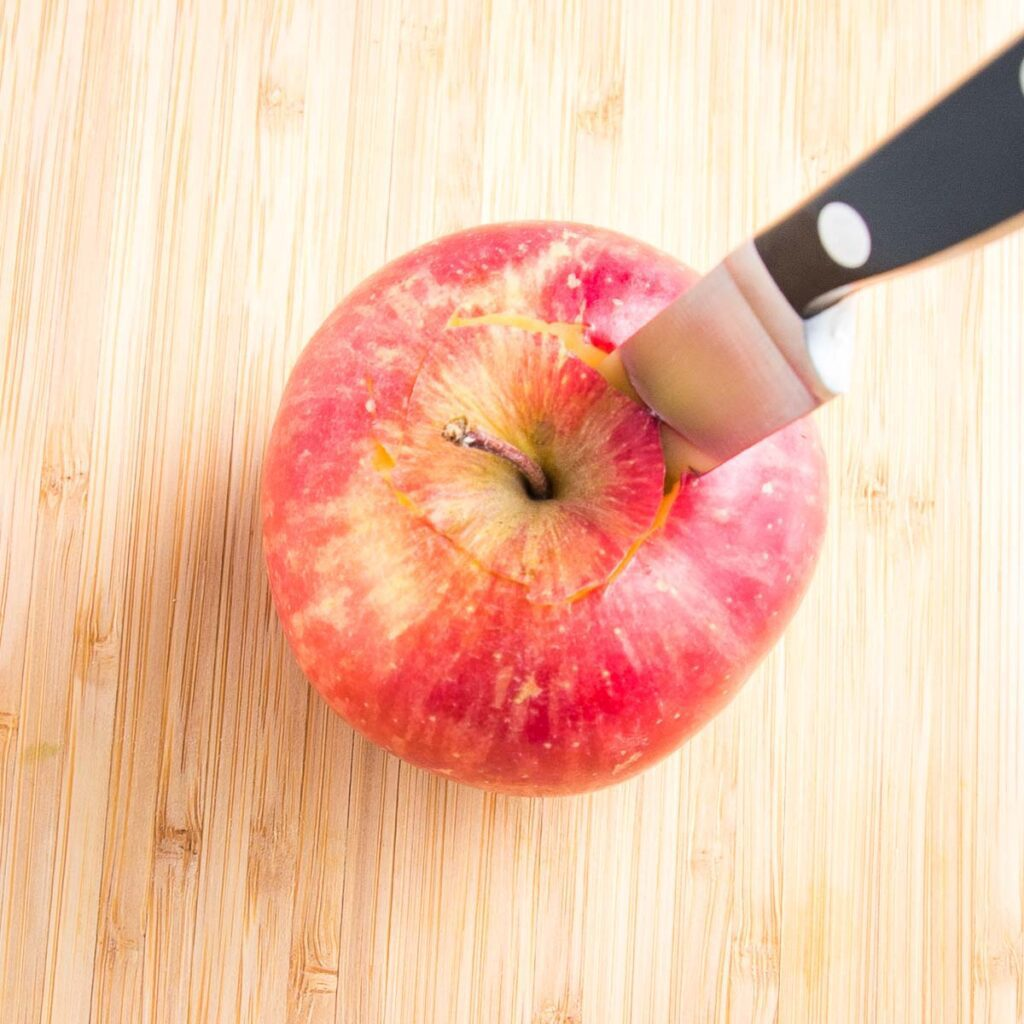 Close up of a honey crisp apple and a small paring knife inserted on the top for removing the core.
