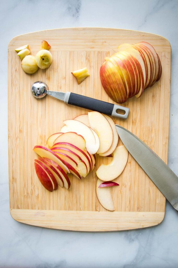 Wooden cutting board with red apple sliced thinly in two halves. A melon baller is in the center and the core in the upper left corner.
