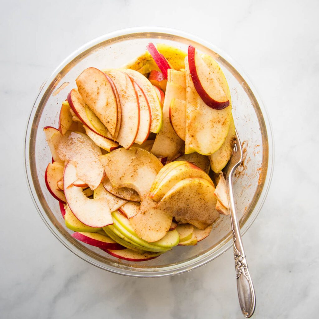 Green and Red Sliced Apples, mixed with apple pie spices, in a large glass bowl.
