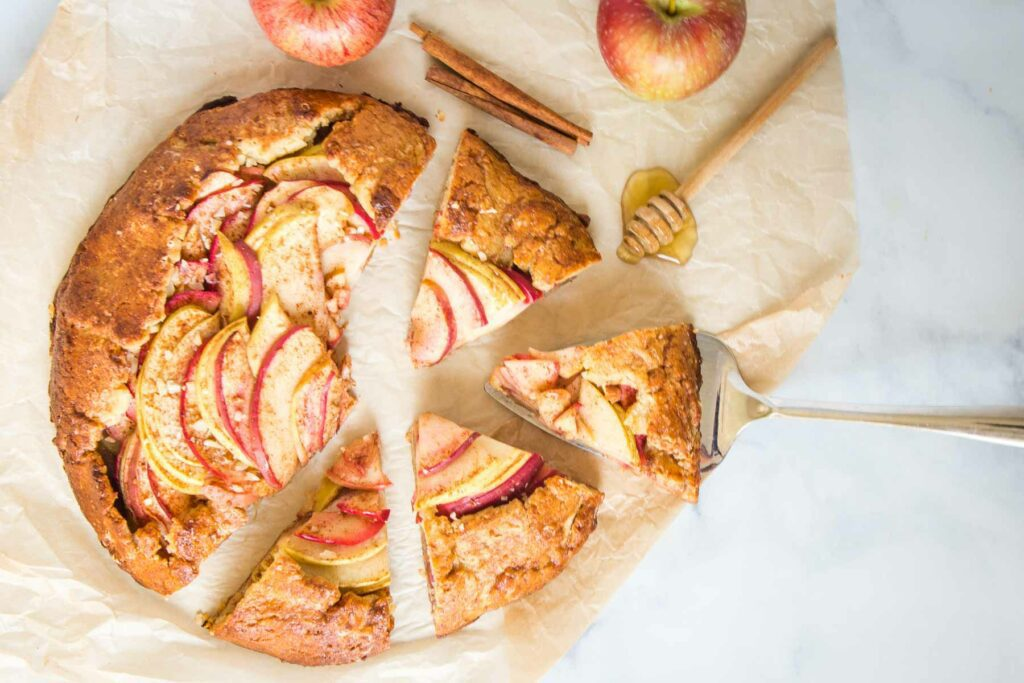 apple galette on a piece of parchment paper, some of it sliced, and also some cinnamon sticks and apples.