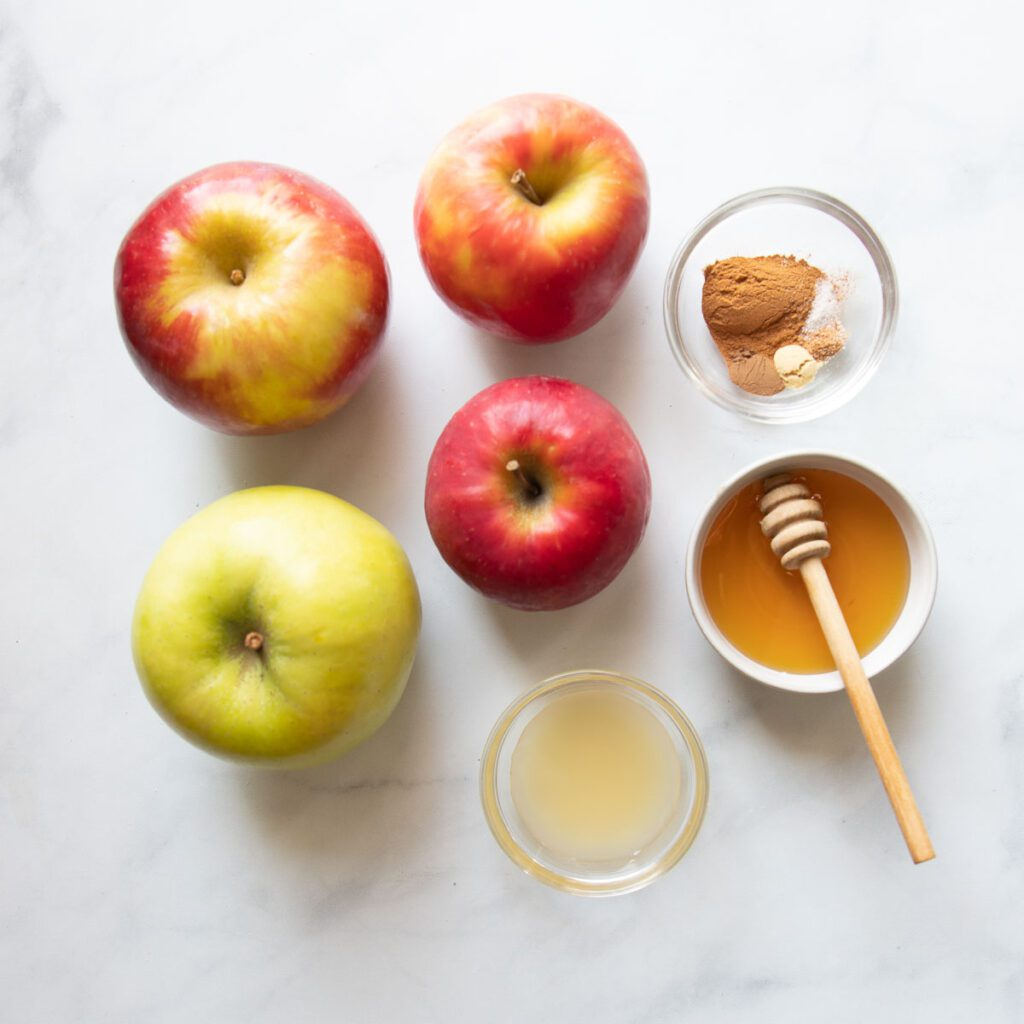 Ingredients for apple galette filling:  an assortment of red and green apples, a small dish with spices, a little bowl of honey and a small glass dish with lemon juice