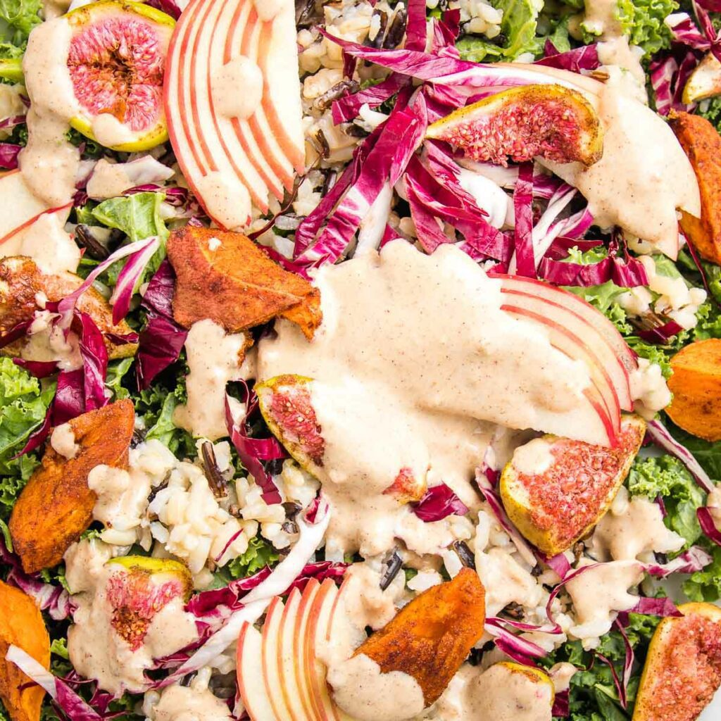 close up of fall harvest salad:  kale, radicchio, slices of apples, roasted sweet potatoes, fresh figs, and a creamy light peach colored dressing