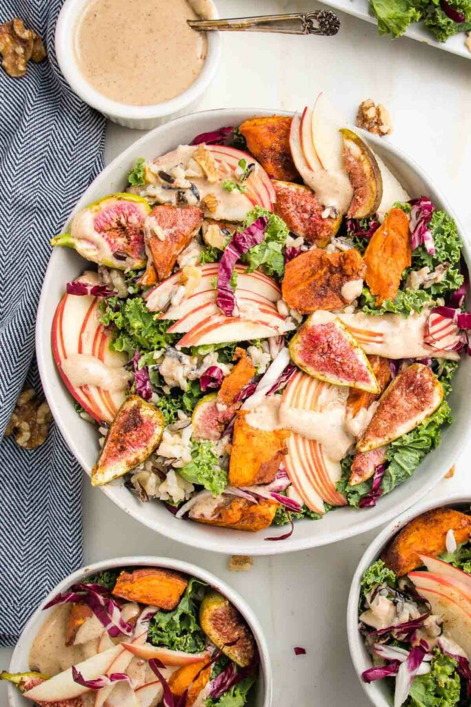 Large bowl with harvest kale salad, loaded with roasted sweet potatoes and figs, sliced apples, wild rice and drizzled with apple vinaigrette. There are two small bowls with same salad and a small white dish of extra dressing.