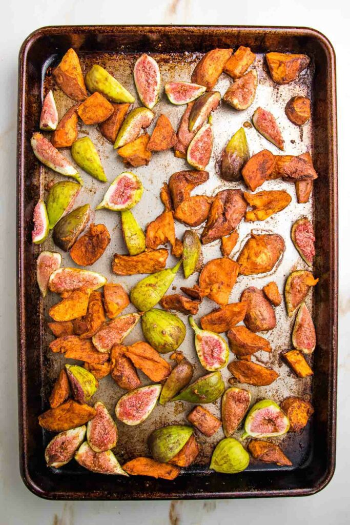 Rimmed sheet pan with roasted sweet potatoes and halved fresh figs.  Roasted with cinnamon, cumin and sea salt.