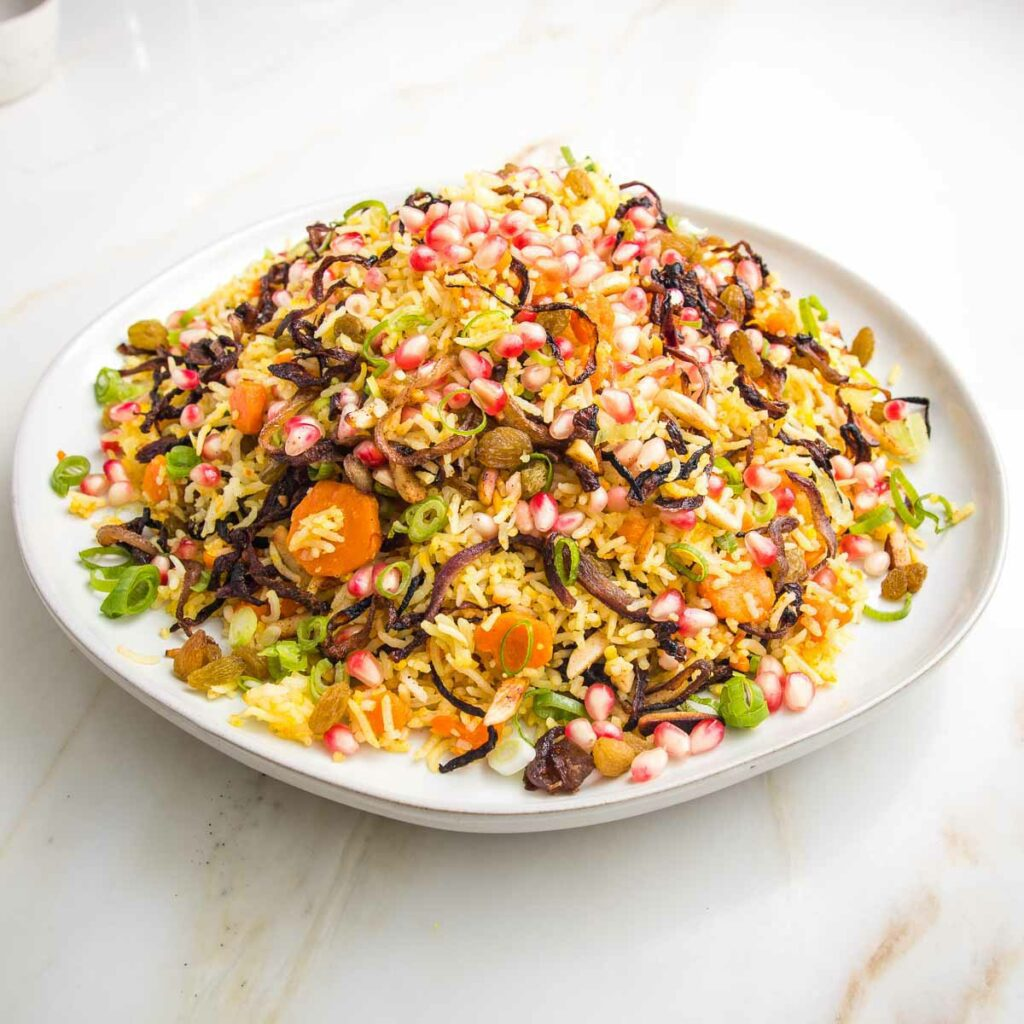White rimmed plate filled with jeweled rice: rice, carrots, raisins, caramelized onions, almonds, scallions.