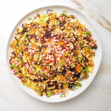 White rimmed plate with a rice dish that's loaded with colorful things like pomegranate seeds, scallions, carrots, golden raisins, caramelized onions and almonds