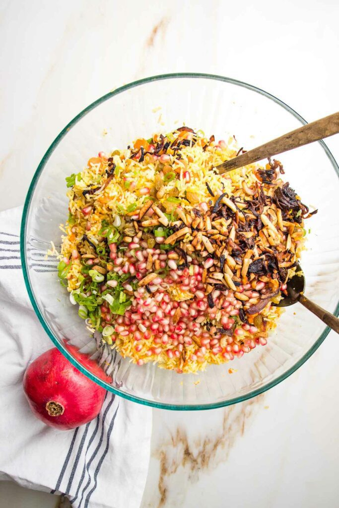 Large glass bowl filled with yellow rice, sliced scallions, pomegranate seeds, golden raisins and caramelized onions.