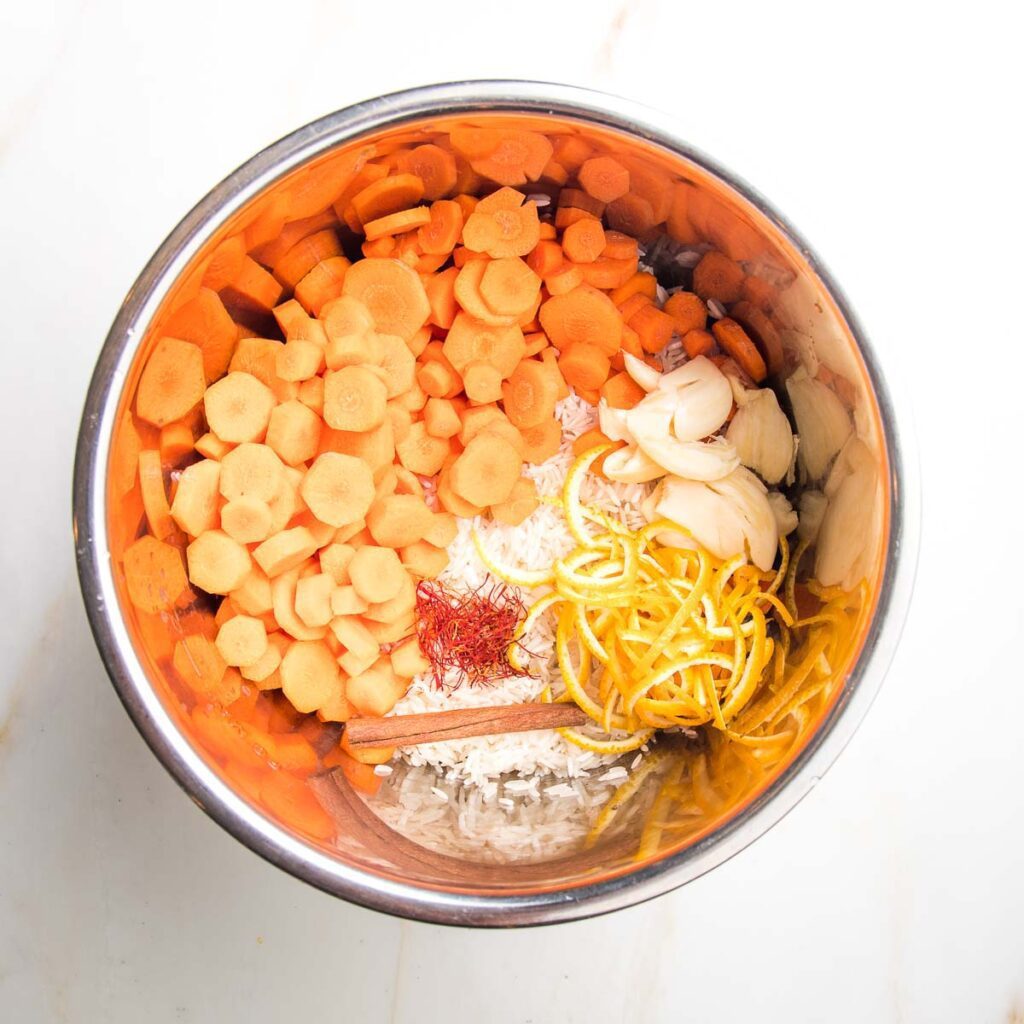 Ingredients in the instant pot: sliced carrot rounds, basmati rice, orange peels, cinnamon stick, whole smashed cloves of garlic, saffron threads.