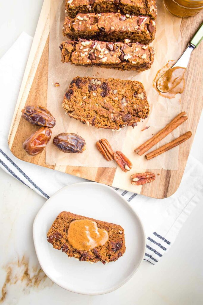 Slices of pumpkin bread with chocolate chips and pecans on a piece of parchment on a cutting board. In the foreground there is a white rimmed plate with a slice of pumpkin bread and a dollop of almond butter on top.