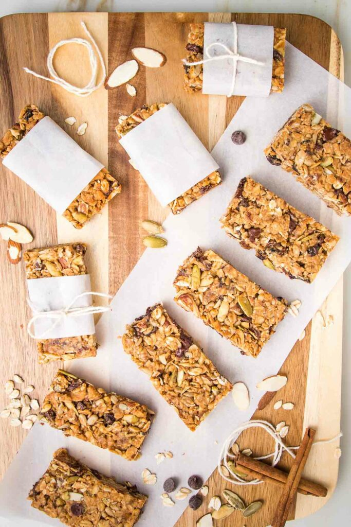 Wooden board with granola bars lined up on a piece of parchment. Also are some bars wrapped in parchment and tied with a kitchen twine. Some cinnamon stick and loose nuts and chocolate chips are strewn about.