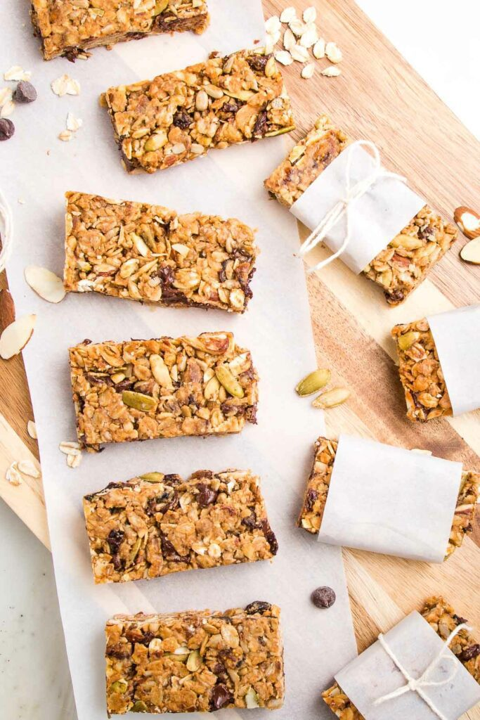 Crunchy granola bars lined up on a sheet of parchment on top of a wooden board.  THere are a few wrapped in parchment strips with a kitchen twine tied around it.