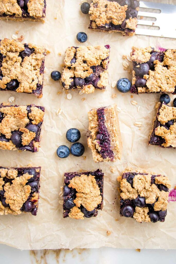 Unbleached parchment paper with squares of blueberry crumble bars.  One turned on its side so you can see the center jammy layer.